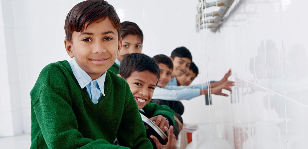 children using drinking water fountain at school