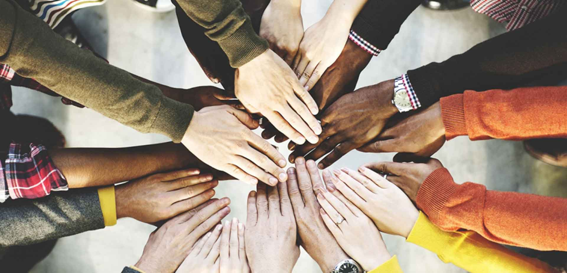 Hands of people of different races hold together