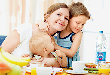 Mother, son and daughter looking happy at breakfast table
