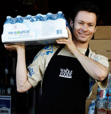 a man is carrying a pack of Nestlé Waters Resizrce bottles