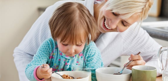Mother and daughter eating breakfast cereal