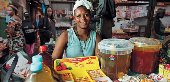 A woman sells Maggi seasoning cubes in Conakry, Guinea