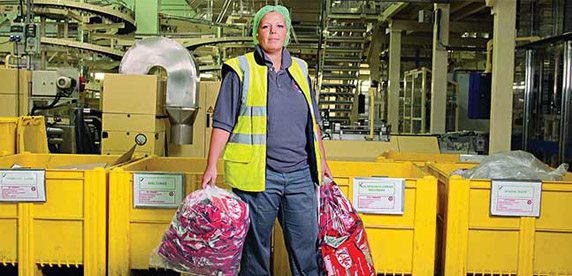 A worker holds bags of recycling in Nestlé's York factory