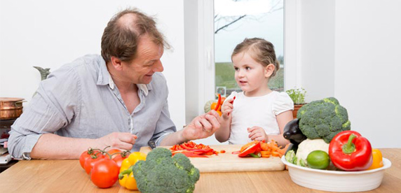 adult prepares salad with a child