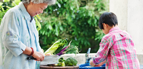 Woman and child chopping vegetables