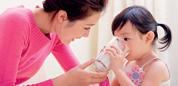 Mother holding glass of milk for child