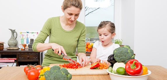 Mother and child chopping vegetables in the kitchen
