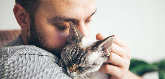 man with cat snuggle moment