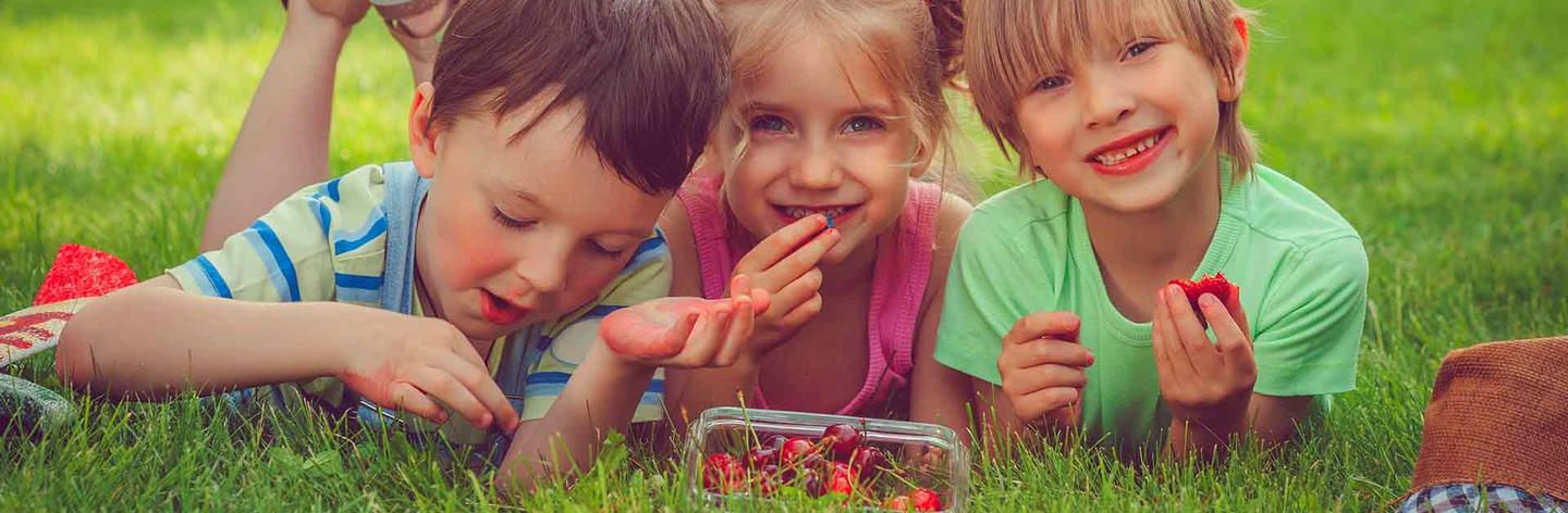 Three kids eating cherries outside